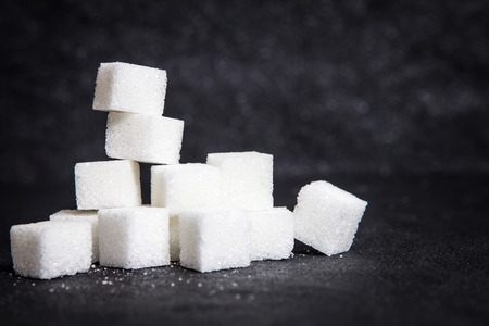 cloose up the white sugar cubes on black stone plate background Stock Photo