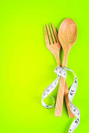 the wooden fork and spoon tied with Measuring tape on vibrant green background in concept meal of healthy and diet
