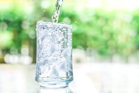 tomando agua: un vaso de agua fría con un poco de flujo de agua hacia abajo un movimiento Foto de archivo