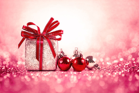 Silver and red Christmas balls and gifts on sweet red pink glitter lighting  background