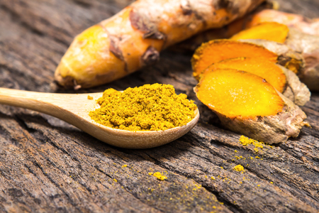 selective focus the turmeric powder in spoon and roots on wooden plate Archivio Fotografico