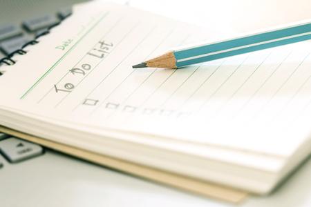 小さなメモ帳で計画リストを行うに手書きで木製の鉛筆を閉じる