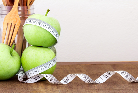 measuring instrument: the green apple with Measuring tape on wooden background in concept of healthy and diet