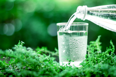 The glass of cool fresh water on natural green background