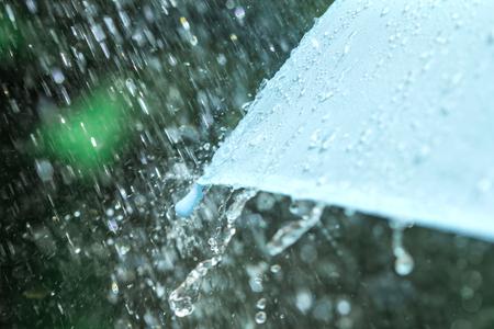 lluvia paraguas: enfoque selectivo de cerca una parte de la sombrilla que tiene gotas de lluvia que caen, DOF bajo