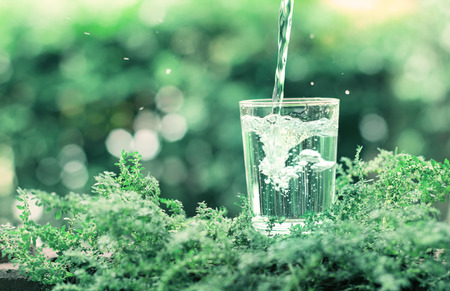water flowing: The glass of cool fresh water on natural green background