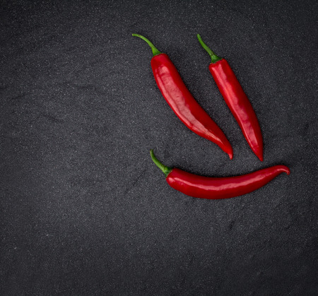the chili pepper on black stone background