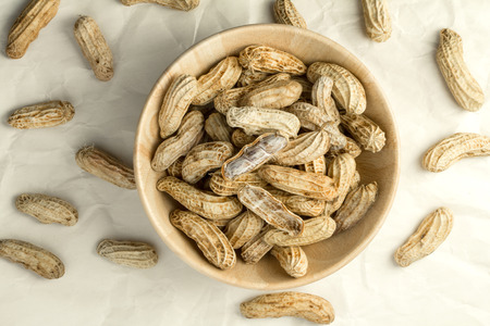the boiled peanuts in wooden cup on crumpled paper