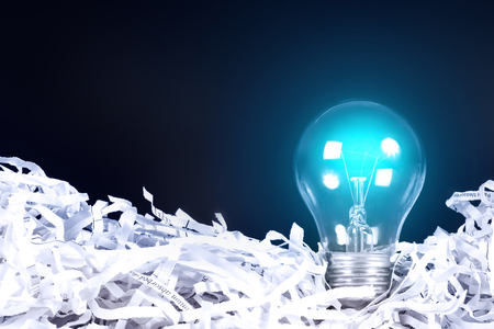 waste prevention: the blue Light bulb glowing place on shredded recycled paper on black background , idea innovation concept Stock Photo