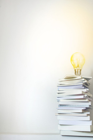 Close up glowing light bulb on book stacked  with concrete wall background , education and learning concept