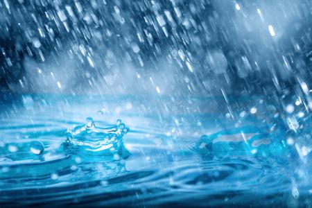 Gotas azules que caen del clima de fuertes lluvias en el agua