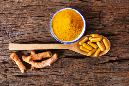 the turmeric powder , capsule and roots curcumin on wooden plate Archivio Fotografico