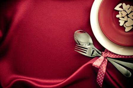 愛ディナー コンセプトの赤いシルク生地にスプーンとフォーク白空板と赤いハート 写真素材