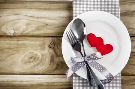 愛ディナー コンセプトの木製のテーブルのスプーンとフォークの白い空板と赤いハート