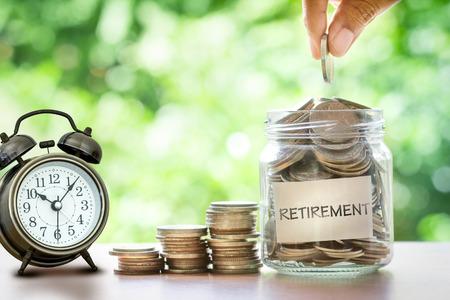 Mano che mette Monete in vaso di vetro con la sveglia retrò per il tempo di risparmio di denaro per il concetto di pensionamento