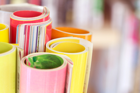Close up edge of colorful magazine stacking roll with  blurry bookshelf background for publication and publishing concept , extremely shallow DOF