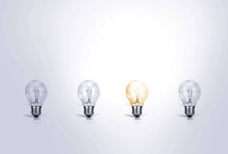 Outstanding creative idea background concept . one Light bulb glowing among a group light bulbs. Stock Photo