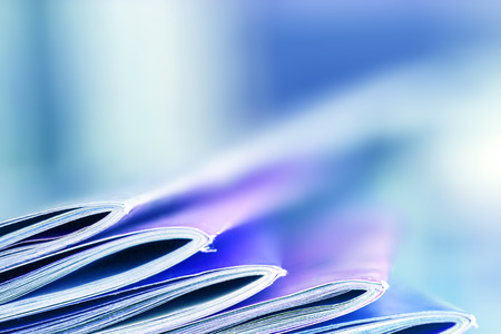 Close up edge of colorful magazine stacking with  blurry bookshelf background for bublication and publishing concept , extremely DOF