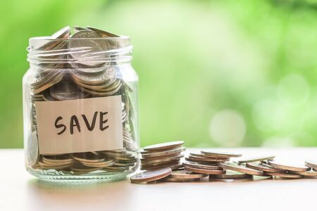 money concept: Coins in glass jar for money saving financial concept