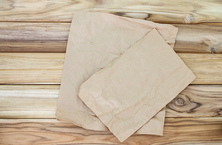 Crumbled cooking or baking paper sheet place on wooden table Zdjęcie Seryjne - 66265232