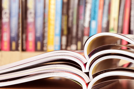 close up stacking of opened magazine with blurry bookshelf background , extremely shallow DOF Stock Photo