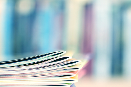 Close up edge of colorful magazine stacking with  blurry bookshelf background for publication and publishing concept , extremely shallow DOF