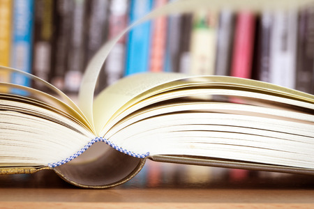 Close up opened book page with blurry bookshelf background for education and publication concept , extremely shallow DOF Stock Photo
