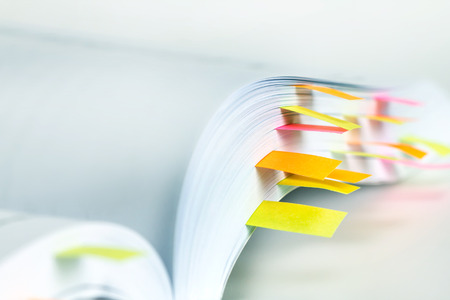 Close up White book marked by sticky note