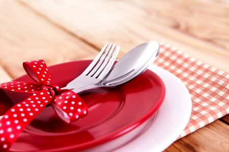 close up dinner setting fork and spoon on plate on wooden background Stock Photo