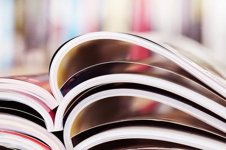 close up stacking of opened magazine with blurry bookshelf background , extremely shallow DOF 写真素材
