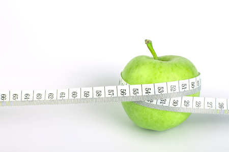 測定テープ健康の概念や食生活の白い背景の上の緑のリンゴ