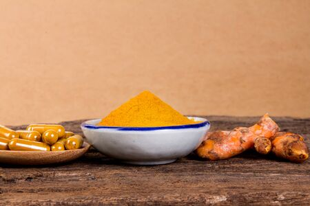 tumeric: the turmeric powder and capsule and roots curcumin on wooden plate