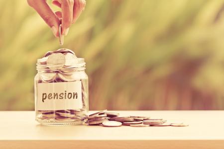 Hand die Muntstukken in glaskruik zetten voor tijd aan geldbesparing voor pensioenconcept, uitstekende retro kleurentoon