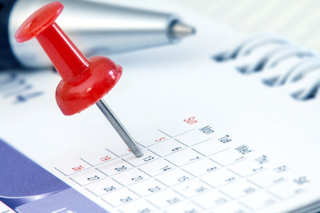 Red pushpin on calendar page for remind and marked important events Zdjęcie Seryjne