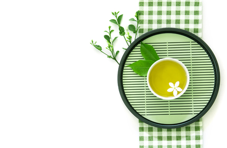Top view shot of a hot cup of tea with green leaf decoration  with green napkin on white background , Organic green Tea ceremony time concept Banco de Imagens