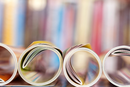 Close up edge of colorful magazine stacking roll with  blurry bookshelf background for bublication and publishing concept , extremely DOF