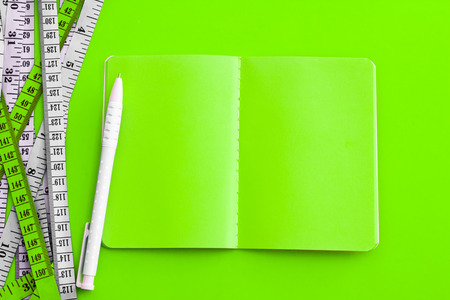 Diet control concept background. Colorful of Measuring tape on vibrant color  background with book diary notepad and  pen for healthy fitness  background.