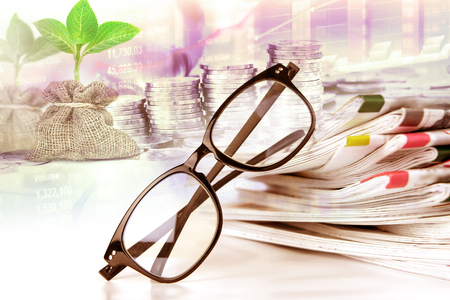 selective focus on reading eyeglasses with stacking of the newspaper background ,business information concept Stock Photo
