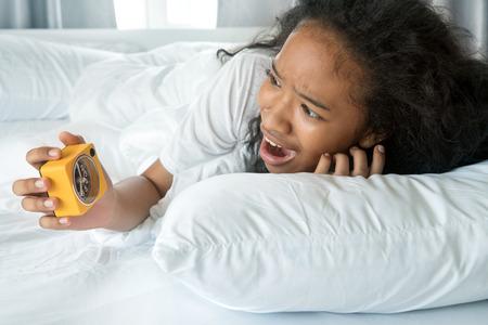 Amerikanische niedliche Mädchen suchen Wecker mit aufwachen spät und Panik in einem Morgen auf sauberen weißen Bett Zimmer Standard-Bild