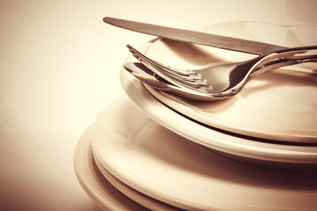 close up dinning the silverware fork , spoon and knife with dish on white background and text space Stock Photo