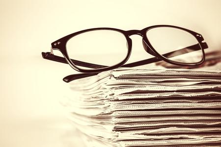 selectieve aandacht op de lezing brillen met het stapelen van krant achtergrond, vintage retro kleurtoon Stockfoto