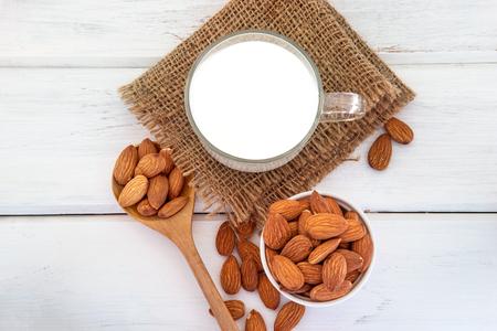 bouchent la vue de dessus de lait d & # 39 ; amande saine dans le verre à boire avec graine de citrouille blanche et une cuillère en bois sur une plaque blanche plaque de bois avec espace copie