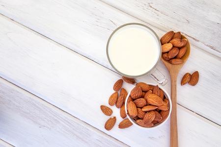 Schließen Sie herauf Draufsicht der gesunden Mandelmilch im Trinkglas mit Samen in der weißen Schale und im hölzernen Löffel auf weißer Holztischplatte mit Kopienraum