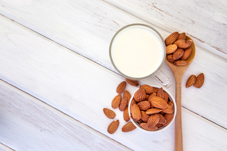 Sluit omhoog hoogste mening van gezonde amandelmelk in het drinken van glas met zaad in witte kop en houten lepel op witte houten lijstplaat met exemplaarruimte
