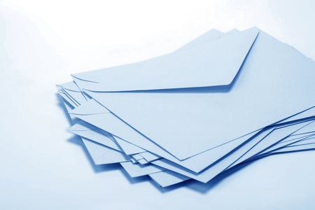 close up Stacking of  envelopes and mail letter paper on white background Stock Photo