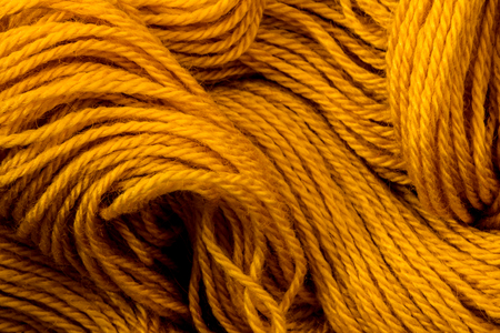 Close up golden yellow yarn thread as abstract  background