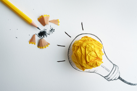 yellow pencil with yellow crumpled paper ball and hand drawn a light bulb , creative innovation idea symbol concept