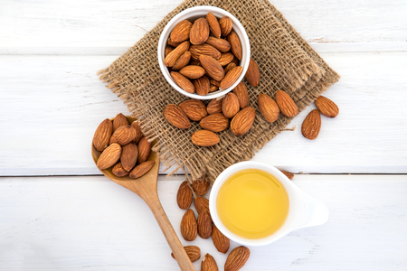 holistic view: Close up almond oil in the bottle and almond seed in white cup for oil massage and spa treatment ingredient on white wooden table background , top view or over head shot with copy space