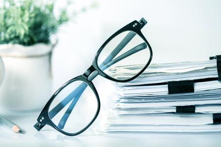 Office 종이, 비즈니스 작업 문서 및 정보 데이터 개념의 스태킹에 검은 독서 안경을 닫습니다.