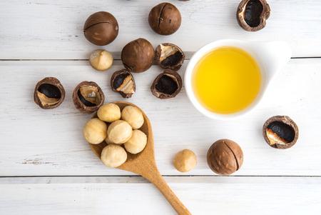 De Macadamia notenolie en geschilde macadamia noot op witte tafel,? Gebruik voor een gezonde huid en haar en natuurlijke genezing van olie behandeling, overhead en bovenaanzicht